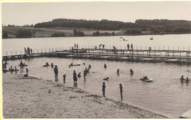 Lata 70. lub 80. Plaża w Sępólnie Krajeńskim. Po drugiej stronie jeziora widoczny las i teren osiedla domów jednorodzinnych z rzadką jeszcze zabudową.