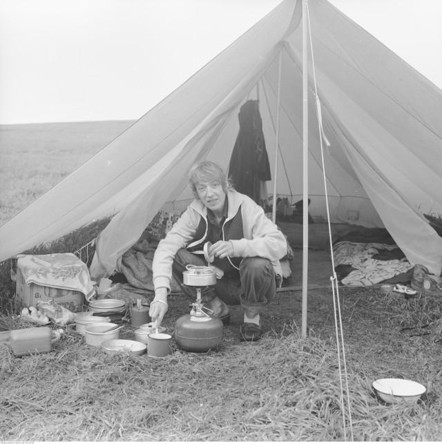 """Bezmiechowa Górna  Grażyna Rutowska gotuje posiłek w namiocie. Widoczny komplet naczyń aluminiowych od kuchenki turystycznej """"Wisła"""" i butla gazowa z nakręcanym palnikiem.  Data: 1983-08"""
