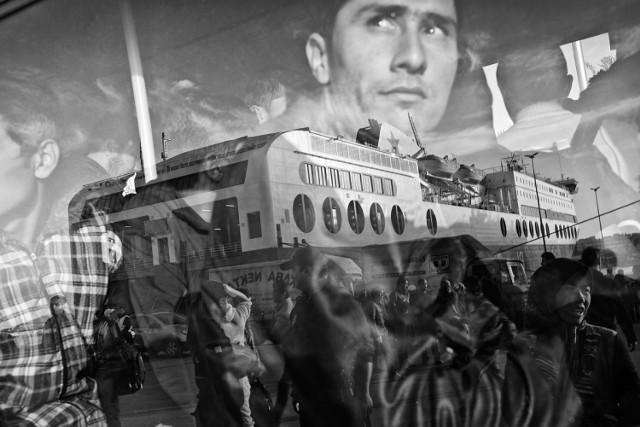 """""""Grecja. Migranci i uchodźcy opuszczający port w Pireusie. Ponad milion ludzi, głównie z Syrii, Iraku i Afganistanu, przybyło do Europy w 2015 roku. Ponad 80 proc. z nich wybrało morską przeprawę przez cieśniny Morza Egejskiego z wybrzeża Turcji na greckie wyspy. Zdjęcie pochodzi z fotoreportażu dokumentującego pierwsze dni uchodźców i migrantów na europejskiej ziemi. 17 października 2015"""""""