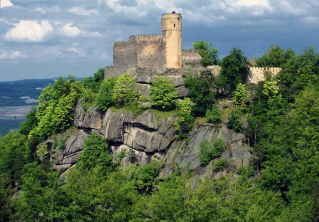 """Decyzję o zwiedzaniu zamku Chojnik należy podjąć ze świadomością, że zanim znajdziemy się na miejscu, czeka nas godzinne podejście pod górę o tej samej nazwie. Do obiektu prowadzi kilka dróg. Możemy je pokonać zarówno pieszo, jak i na rowerze. Po drodze warto zwiedzić Jaskinię Przemytników. Zamek górujący nad Piekielną Doliną można zwiedzić w godzinach od 10.00 do 17.00. Na miejscu możemy również spróbować się w strzelaniu z kuszy. Szczególnie, że na zamku organizuje się coroczny turniej kuszników """"O złoty Bełt Chojnika"""". W zamku możecie skorzystać z oferty schroniska i restauracji.  Zobacz na kolejnych slajdach najpiękniejsze zamki Dolnego Śląska - posługuj się myszką, klawiszami strzałek na klawiaturze lub gestami"""