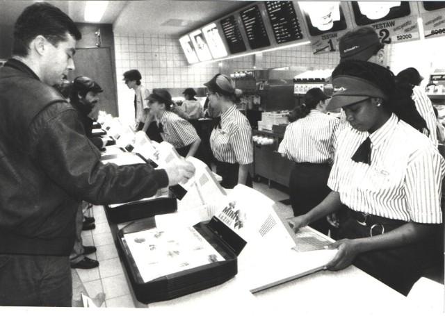 """Pierwszy McDonald's w Polsce został otwarty w 1992 roku w Warszawie. Poznań """"doczekał się"""" lokalu tej sieci dwa lata później. McDonald's w stolicy Wielkopolski był dziesiątą placówką w Polsce. Zlokalizowano go przy ul. 27 Grudnia na parterze DH Domar (naprzeciwko Okrąglaka). W tym miejscu działa też do dziś. Zobaczcie, jak to miejsce wyglądało ponad 20 lat temu!  Przejdź do kolejnego zdjęcia --->"""
