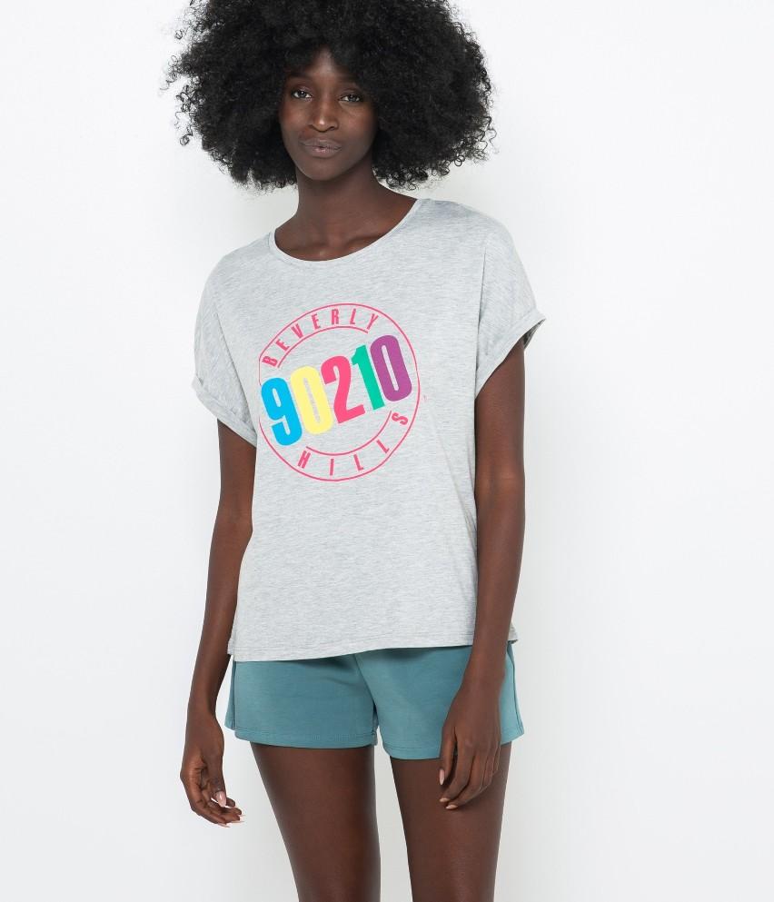 Wieczór chillout, otulający, ciepły? Jeśli tak właśnie chcesz się spędzić wolny czas, sięgnij po wspaniały T-shirt homewear i zrelaksuj się! Dekolt w kształcie łódki, bawełniana miękkość i ochrona. A do tego oldskulowy napis: « 90120 Beverly hills »! Modelka ma 177 cm wzrostu i prezentuje produkt w rozmiarze 38.