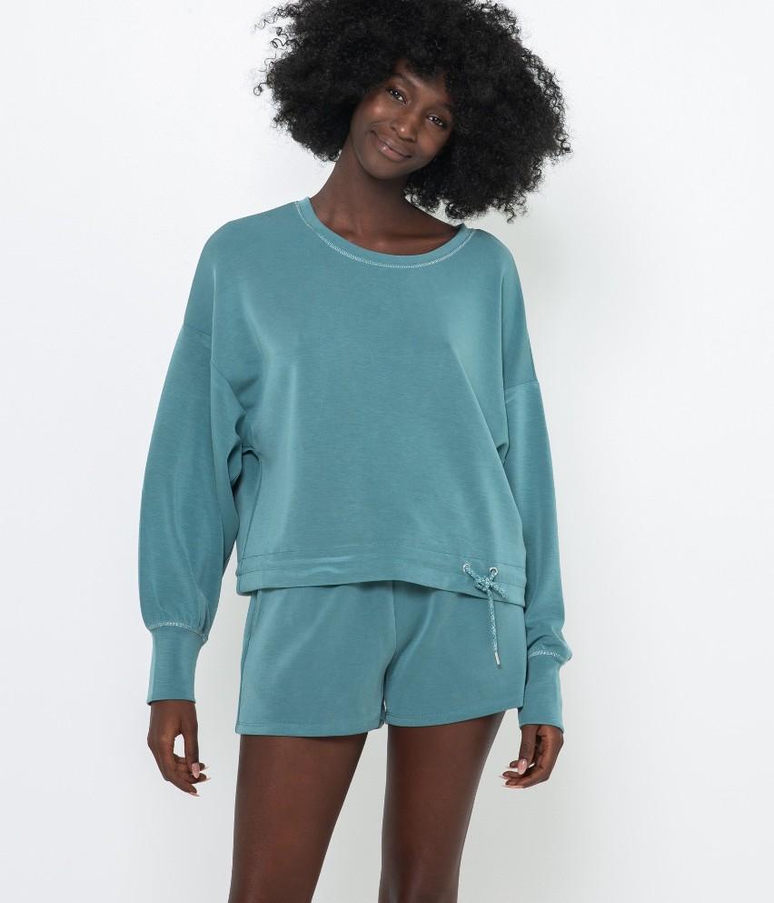 Wygodna bluzka homewear z fantazyjnym wiązaniem przy wykończeniach dołu. Uwagę zwracają też błyszczące nitki przy dekolcie, dodając kobiecości i lśnienia. Świetnie będzie pasować do szortów o numerach  530536. Modelka ma 177 cm wzrostu i prezentuje produkt w rozmiarze M.