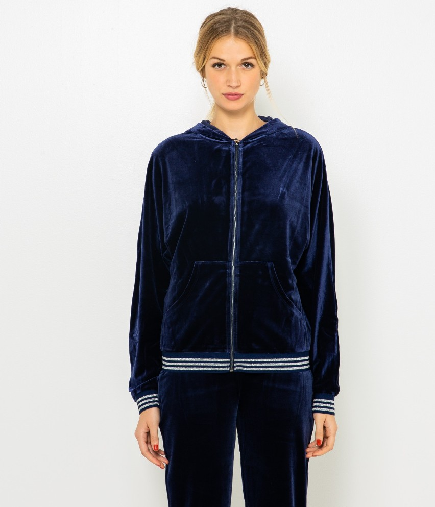 Szukasz czegoś na luźne wieczory w tonach chill out? Sięgnij po sweter z kapturem, którego aksamitna tkanina i zgrabny krój cieszą urokiem i wygodą. Ten sweter świetnie dopasujesz do ulubionych dresowych lub  domowych. Odkryj otulenie, luz, wygodę. Ciesz się fantazyjnymi rozwiązaniami, by również i w domu, wyglądać trendy. Modelka ma 175 cm wzrostu i prezentuje produkt w rozmiarze M.