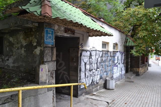 Budynek dawnego szaletu miejskiego popadł w ruinę. Wygląda tragicznie, do tego jest pomazany graffiti. Jeśli uda się rozstrzygnąć przetarg, to zostanie wyburzony, a w jego miejscu powstanie nowa toaleta publiczna.   Zobacz kolejne zdjęcia. Przesuń w prawo - wciśnij strzałkę lub przycisk NASTĘPNE