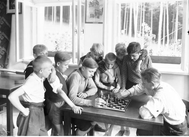 Przygotowaliśmy dla was galerię archiwalnych zdjęć z dziecięcej codzienności. Niektórym z was na pewno zakręci się łezka w oku! Pamiętacie takie dzieciństwo?  Gra w szachy na koloniach letnich, 1938 rok