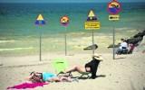 Znaki na plaży w Darłówku. Informują m.in. o zakazie skakania z falochronu