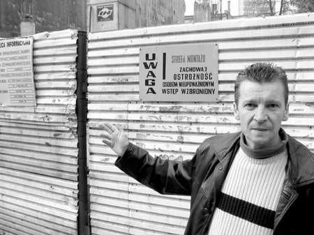 Grzegorz Operhalski wskazuje zrujnowany budynek.