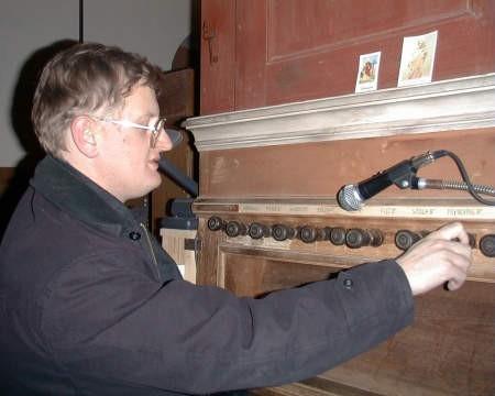 ksiądz Mirosław Romanowski, proboszcz kosobudzkiej parafii przy zabytkowym instrumencie.