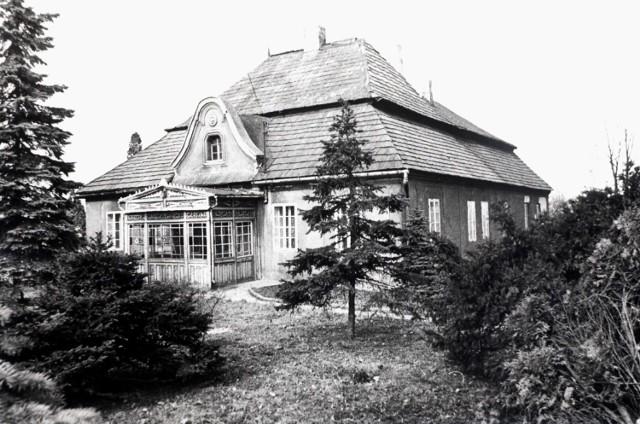 """Plebania w stylu architektury """"dworkowej"""" z 1783 r., rozbudowana w XIX w., przed wejściem pod facjatką oszklona weranda rozebrana w ostatnich latach XX w., około 1930 r."""