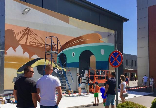 Mural powstał podczas niedawnego Pikniku Rodzinnego, który po kilku latach przerwy Pesa zorganizowała dla swoich pracowników i ich rodzin. - W imprezie uczestniczyło prawie 5 tysięcy ludzi, przygotowaliśmy sporo atrakcji, koncertowały Żuki, goście mogli zwiedzić hale produkcyjne, przejechać naszym pociągiem na Rynkowo - opowiada Maciej Grześkowiak, rzecznik Pesy. Jedną z atrakcji było tworzenie muralu, dzieci mogły przyglądać się powstawaniu muralu, w strefie plastycznej miały kolorowanki z muralem, a w różnych konkursach wśród nagród były koszulki z tym muralem. Mural zaprojektowali i osobiście wykonali nasi młodzi designerzy z Zespołu Rozwoju Produktu - Krzysztof Nogowski, Miłosz Pszczóliński i Marek Gembicki. Swoją stylistyką nawiązuje on do amerykańskich plakatów reklamowych z lat 20 minionego wieku, kolorystyka uwzględnia barwy otoczenia. Mural ozdobił ścianę szczytową budynku stojącego obok parkingu dla gości przy budynku zarządu. - Nie wykluczamy, że w przyszłości powstaną kolejne - zdardza Grześkowiak.