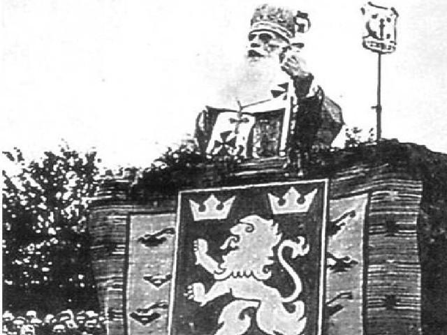 Zdjęcie bpa Jozafata Kocyłowskiego, wykonane podczas II wojny św. na stadionie w Przemyślu, w trakcie błogosławienia żołnierzy niemieckiej dywizji SS Galizien. U dołu herb tego oddziału.