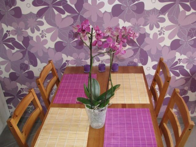 Fioletowa tapeta w jadalniFioletową tapetę i podkładki w kolorze fuksji tonuje ciepłe drewno kuchennego stołu. Do tych naturalnych barw świetnie pasują zielone liście fioletowego storczyka.
