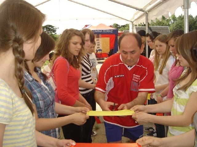 Jedną z konkurencji było przecięcie wstęgi na czas. Samorządowcy starali się jak mogli. Na zdjęciu burmistrz Suraża Sławomir Halicki.
