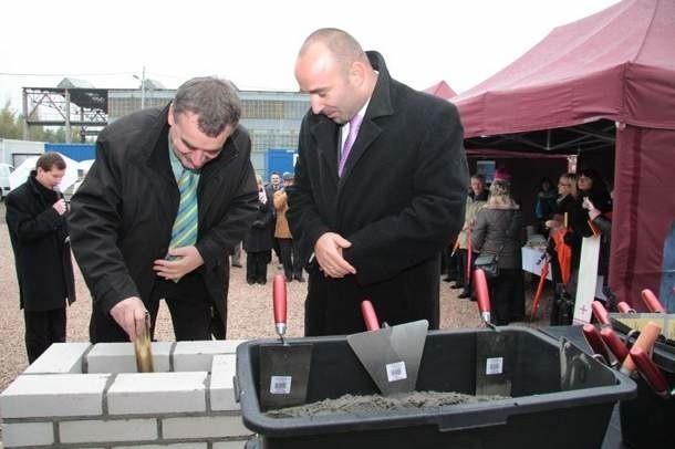 Prezydent Wojciech Lubawski wraz z Szymonem Mazurkiewiczem, dyrektorem Parku, chowają w murze akt erekcyjny.