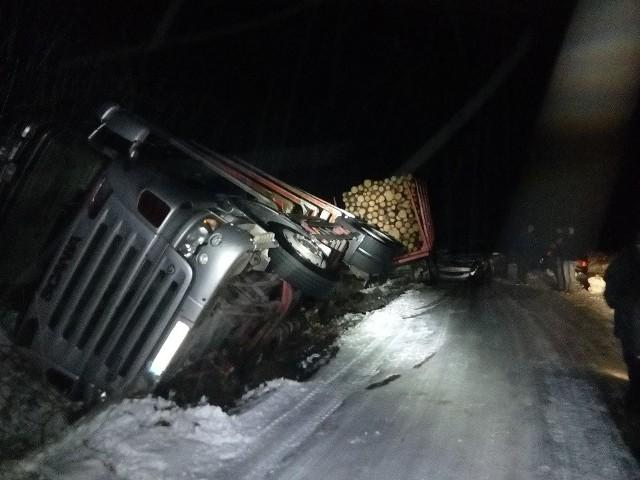 Do groźnie wyglądającego wypadku doszło we czwartek po godzinie 15.00 w miejscowości Rudzie w gminie Gołdap. Ze wstępnych ustaleń mundurowych wynika, że kierujący ciężarową scanią z naczepą, na łuku drogi nie dostosował prędkości do warunków panujących na drodze i wpadł w poślizg, po czym naczepa wyjechała na przeciwległy pas i uderzyła w dwa prawidłowo jadące z naprzeciwka auta. W wyniku zdarzenia tir wpadł do rowu i wywrócił się na bok.