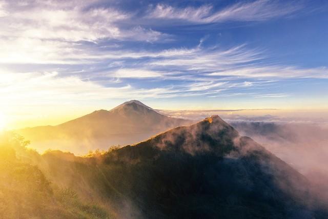 Wulkan Batur, choć wciąż aktywny, dostępny jest dla wszystkich. Wznosi się zaledwie na wysokość 1,700 metrów ponad poziom morza, ale widok z jego szczytu jest naprawdę spektakularny – zwłaszcza podczas wschodu słońca, kiedy to wspaniały krajobraz powoli wyłania się z ciemności.Jeżeli chcemy tego doświadczyć, trzeba wyruszyć około trzeciej nad ranem. Trasa z wioski Toya Bungkah, leżącej na skraju jeziora u stóp wulkanu, zajmuje około dwóch godzin. Pokonanie jej nie jest męczące, jedyne o czym trzeba pamiętać to zakryte obuwie, ponieważ na ścieżce zdarzają się kamienie. Na wierzchołek należy dotrzeć około piątej, ale już wcześniej czeka Was wiele niezapomnianych przeżyć. Jeszcze zanim słońce zacznie wyłaniać się zza horyzontu, cała okolica budzi się wyczuwając nadchodzący dzień. Narastające odgłosy podekscytowanych zwierząt, dźwięki odbijające się od krateru wulkanu, to przeżycie tak emocjonujące, że zanim się obejrzycie będziecie już na szczycie wulkanu. Wystarczy jeszcze tylko chwilę poczekać na świt.Pierwsza łuna słonecznego światła wynurza się zza góry Agung. Promienie stopniowo odsłaniają kolejne szczyty leżące po przeciwległej stronie jeziora Danau Batur. Widzimy jak światło odbija się od jego tafli, w końcu pada także na obręcz krateru na którym stoimy, odsłaniając olbrzymie wulkaniczne stoki pokryte popiołem. Gdzieniegdzie widać nawet parę unoszącą się nad aktywnymi pęknięciami. Ten widok uświadamia nam, że rzeczywiście stoimy na wulkanie, na najaktywniejszym sejsmicznie obszarze na całym Bali! To najlepszy świetlny show, jaki kiedykolwiek przyszło nam oglądać.Z pewnością trudno o lepszą śniadaniową scenerię, dlatego bardzo często zwieńczeniem wyprawy jest wspólne śniadanie – jajka na twardo gotowane bezpośrednio nad parą wydobywającą się ze skalnych szczelin.fot. r.pl