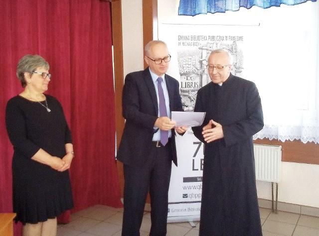 Marek Wojtas, wójt Pawłowa wręcza księdzu Adamowi Orczykowi dyplom Przyjaciela Biblioteki, obok Teresa Sobczak- dyrektor biblioteki.