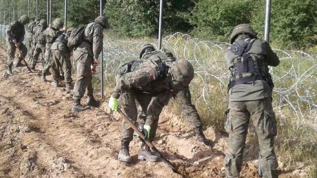 Polscy żołnierze stawiają ogrodzenie z drutu kolczastego na granicy z Białorusią