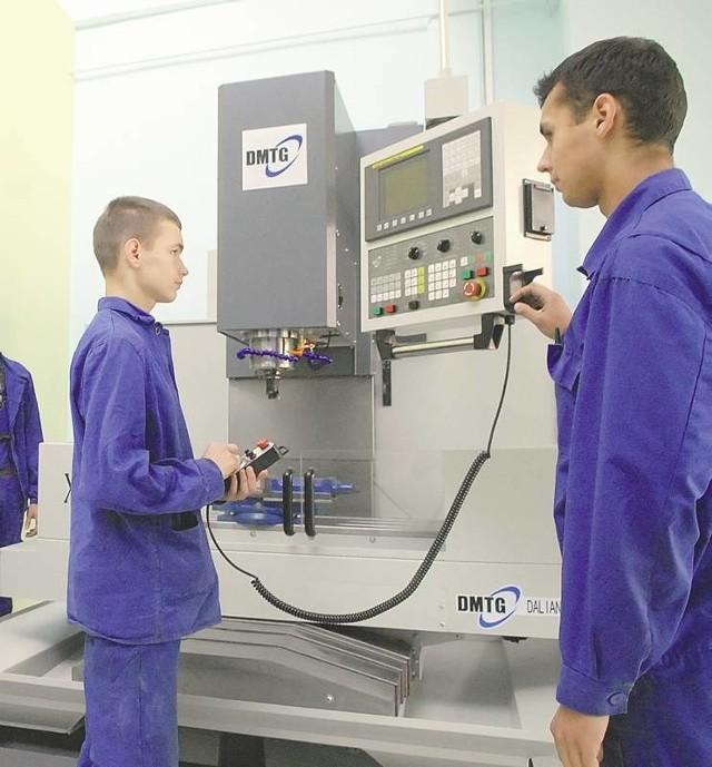 Damian Gąsiorowski i Patryk Łęgowski prezentują urządzenia w pracowni obrabiarek numerycznych