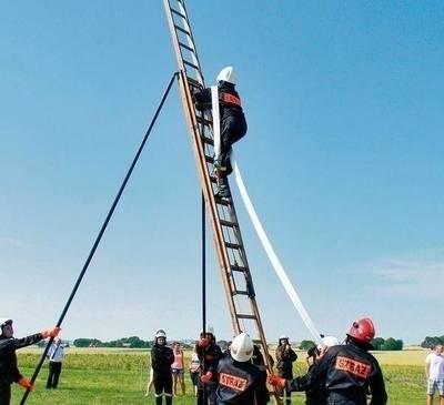 Drużyna kobieca ze Szrabi wspina się po strażackiej drabinie... Fot. Klaudia Skrężyna