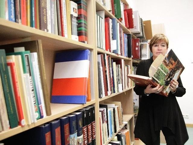 Halina Brzezińska-Stec, dyrektor uniwersyteckiej biblioteki prezentuje dzieła z księgozbioru prezydenta Ryszarda Kaczorowskiego, które trafiły do Białegostoku.