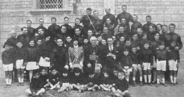 Gino Busi w Ekwadorze (siedzi po lewej ręce duchownego pośrodku). W latach 1928-1930 był włoskim konsulem w Guayaquil