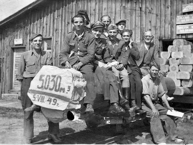 5 sierpnia 1949 roku. Na zdjęciu są pracownicy tartaku: Wojtalik (stoi po lewej), Myk (pierwszy siedzący), Kowalski (trzeci siedzący) i Bolesław Malek (drugi plan,  bez czapki)