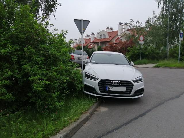 """Ulica Kościelna, osiedle """"Projektant"""". Audi kulturalnie zaparkowane na trawniku."""