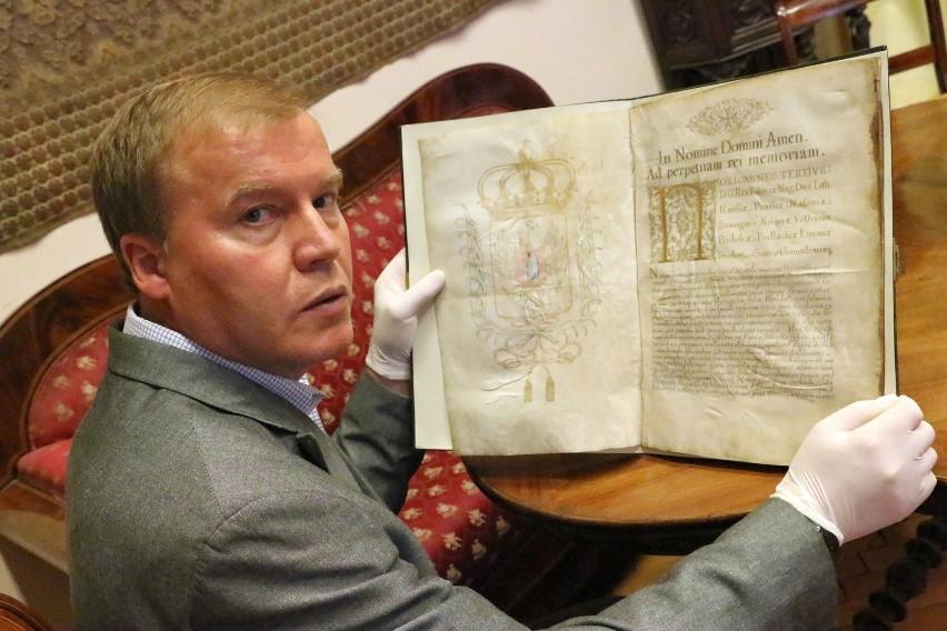 Dyrektor muzeum Andrzej Kirmiel prezentuje indygenat, czyli potwierdzenie przywilejów szlacheckich.