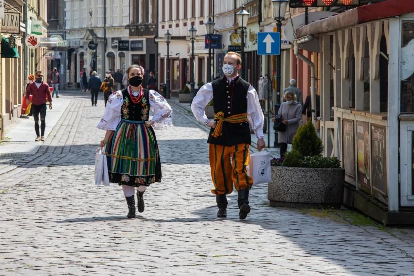 Tancerze w strojach regionalnych rozdawali maseczki...