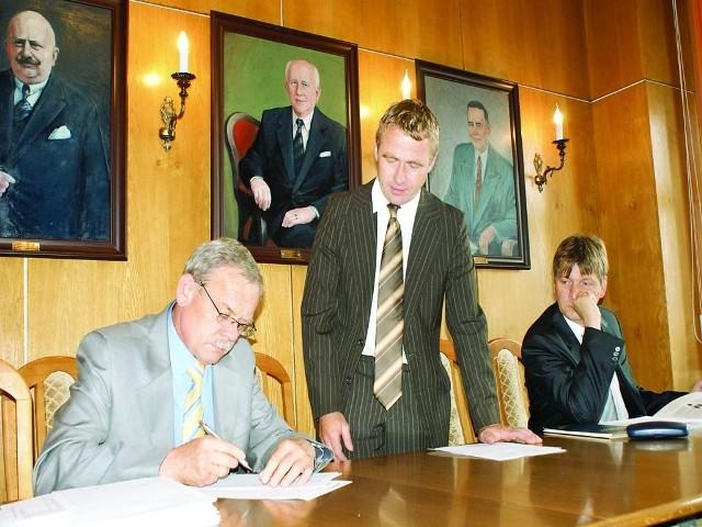 Burmistrz Marek Jankowski ( z lewej) odbiera podpisy od pełnomocnika referendum Romana Stolza i od Roberta Matuszewskiego.