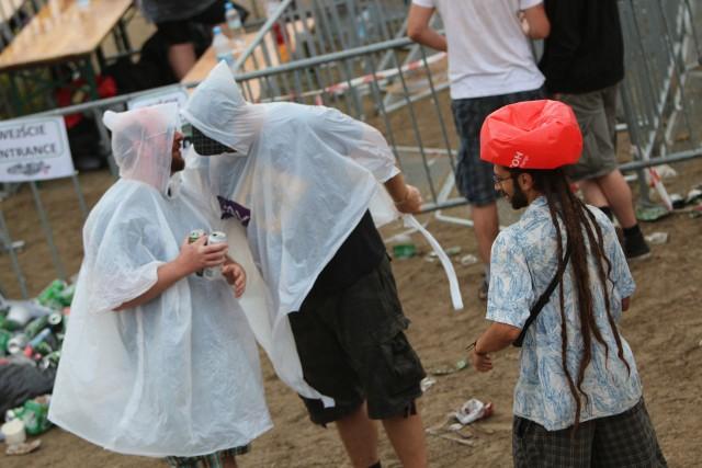 Na chwilę przed godz. 19.00 przez woodstockowe pole przeszły deszczowe chmury. Trochę siąpiło, trochę popadało... Ale na uczestnikach 23. Przystanku Woodstock nie robi to  absolutnie żadnego wrażenia! Wyciągają ze swoich toreb i plecaków przeciwdeszczowe peleryny i parasole. Jak ich nie mają, to chowają głowy pod kurtkami albo chustami i bawią się dalej. A niektórzy nie robić nic. Sprawiają takie wrażenie, jakby skakali jeszcze wyżej i krzyczeli jeszcze głośniej - taki jest klimat Woodstocku. Zobacz też wideo: Ulewa podczas pierwszego dnia Przystanku Woodstock 2017Przeczytaj też:   oodstock 2017: W błocie taplają się i starzy i młodzi [WIDEO, ZDJĘCIA]