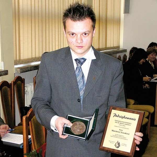 Marcin Nowak z medalem i podziękowaniem.