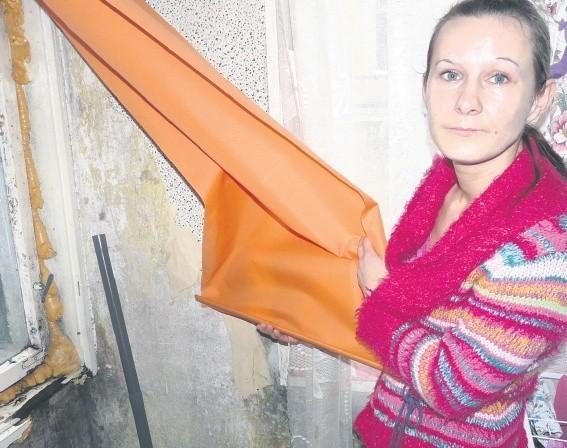 Julita Andrzejewska pokazuje zmurszałe okna, które ledwo się trzymają w futrynach. – W pokoju jest zimno – żali się kobieta.