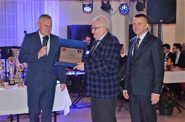 Jerzy Nowakowski (w środku) odbiera pamiątkową paterę za 45 lat działalności w środowisku sędziowskim