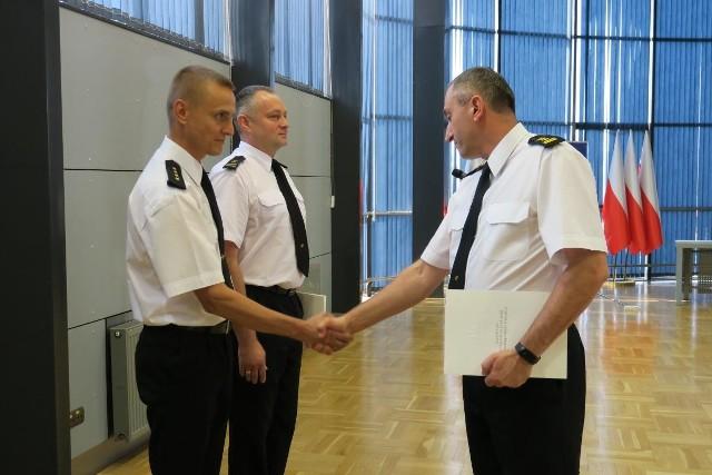 St. kpt. Przemysław Przęczek (z lewej) przyjmuje gratulacje od komendanta wojewódzkiego st. bryg. Piotra Filipka
