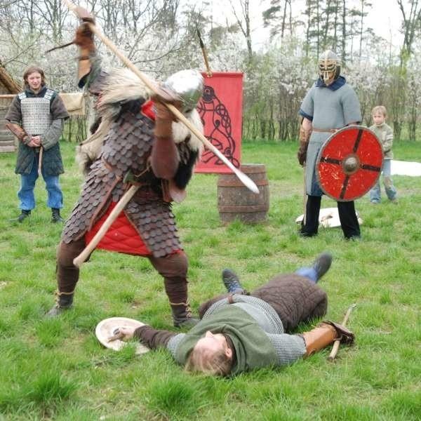 Wojowie trenują walki przed odtworzoną własnymi rękoma średniowieczną chatą w Starym Oleśnie.