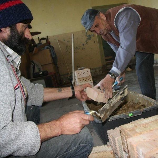 Ryszard Tomaszewski (z lewej) uczy się fachu murarza od mistrza budowlanego Józefa Zimnego.