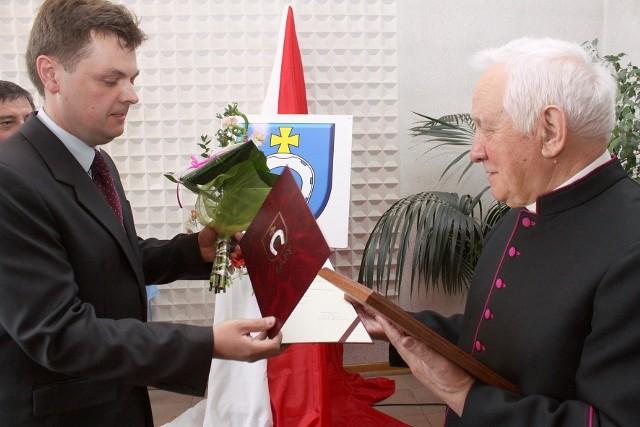 Andrzej Mojkowski przewodniczący rady miejskiej przekazuje dyplom i kwiaty księdzu Tadeuszowi Balukowi.