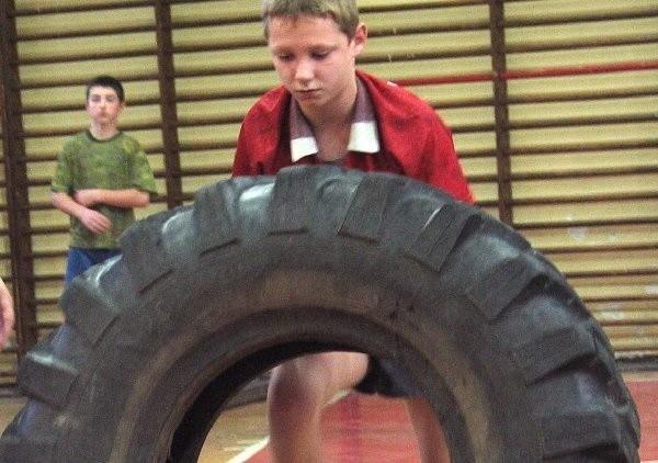 Arek Materka zmaga się z ważącą ponad 150  kilogramów oponą.