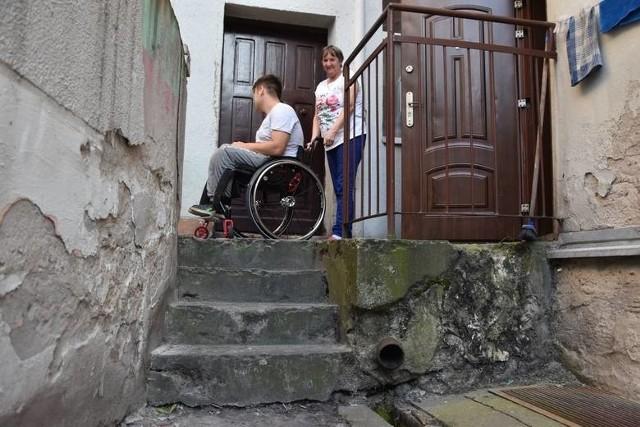 Adrian uczy się zawodu fotografa. By wydostać się z mieszkania choćby do szkoły jego babcia Ewa codziennie musi wózek wraz z nim znosić ze schodów z pomocą sąsiada.