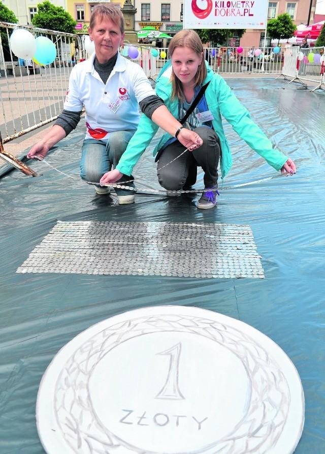 W Rybniku wolontariuszki układały złotówki na taśmie klejącej w metrowe paski, a później ustawiały obok siebie na płycie Rynku