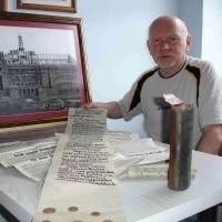 Stefan Orczyc-Musiałek prezentuje ręcznie napisany, niemal dwumetrowy dokument. W tle powiększona fotografia z 1 maja 1931 roku, z uroczystości pozostawienia tulei w wieży.