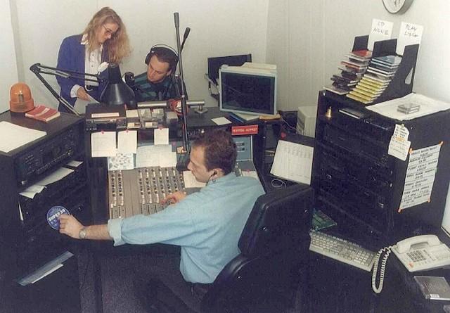 """Didżejka, serce radia Vigor FM (1995). Mariola Ostrowicka i Piotr Merecki przygotowują serwis. """"Za sterami"""" Przemek Brosz."""