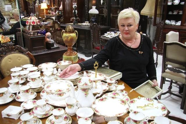 Właścicielka sklepu Maryla Król pokazuje przedwojenną porcelanę.