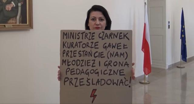 W nagraniu pojawia się także Marta Mazurek, wiceprzewodnicząca Komisji Oświaty i Wychowania RMP, która przed kamerą staje z transparentem.