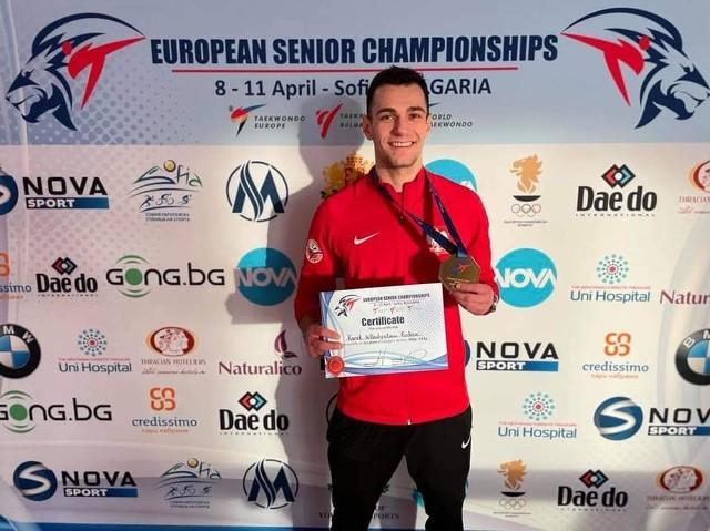 Uśmiechnięty i zadowolony Karol Robak z dumą prezentuje swoją złotą zdobycz z ME w Sofii