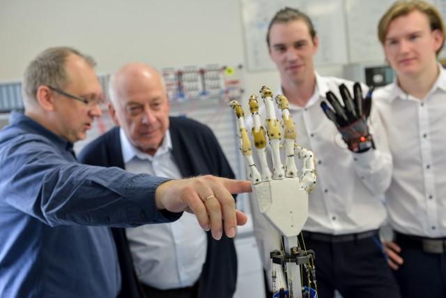 Prof. Mirosław Szmajda (z lewej) pokazuje cyber-dłoń. Obok autorzy prac: Yaroslav Antonchyk (pierwszy od prawej) i Pavlo Sutysskyi.