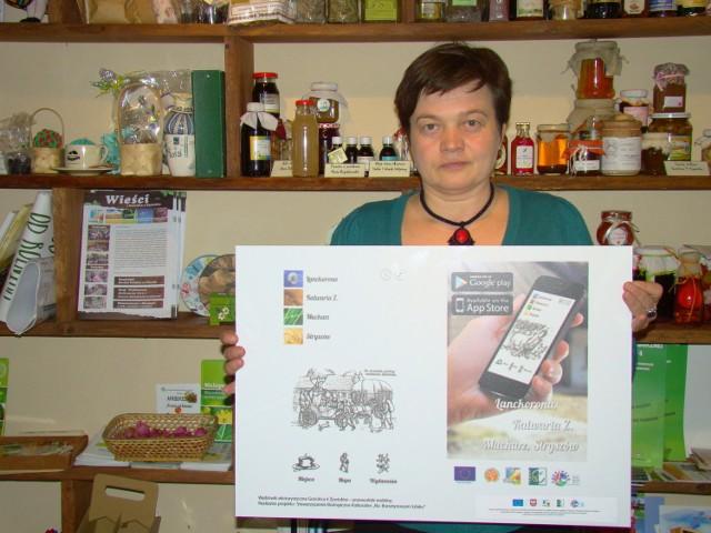 Renata Bukowska, prezes Stowarzyszenia Gościniec 4 Żywiołów, prezentuje planszę z przewodnika mobilnego po gminach.